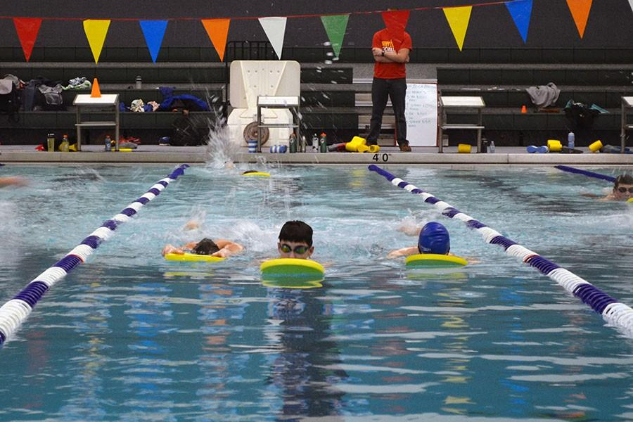 Swimmers use kick boards to improve leg strength during swim practices.