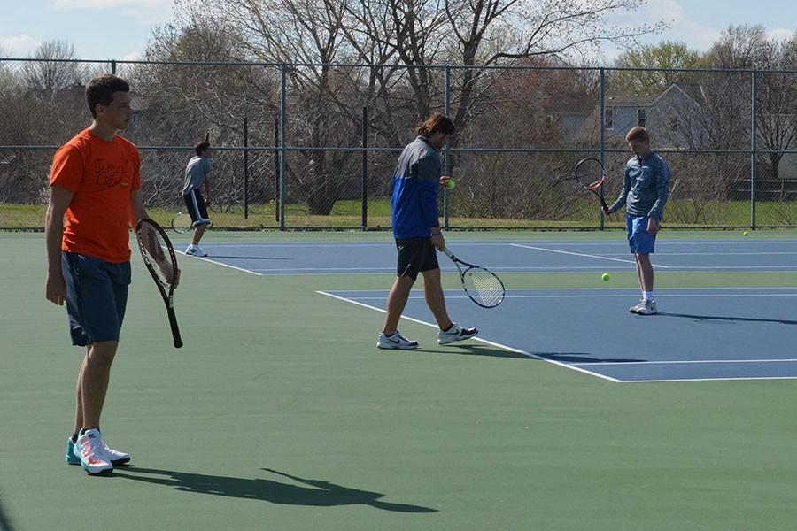 Tennis players practice on the courts behind the school.