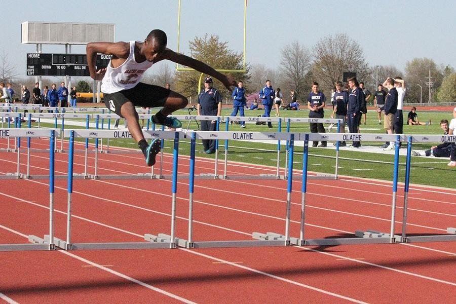 Dakota Okuone, junior, jumping over a hurdle.