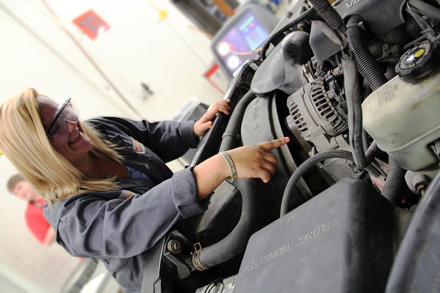 Taylor Noonan, junior, checks the AC fluid on the car she is working on. Noonan has been working on cars for most of her life and this is her first year in the OATC program.  She is involved in the automotive technology program. Even though she is in the program currently, she is not planning on having a career working on cars.