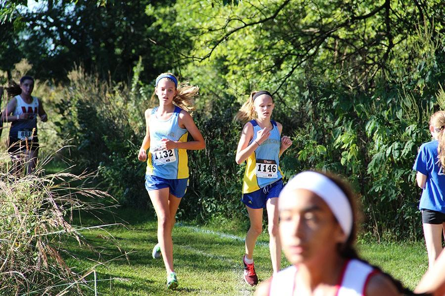 Lilly Engeman, freshman,and Kiley Cox, freshman, race together to help each other keep running and help each other beat there own PR'S.
