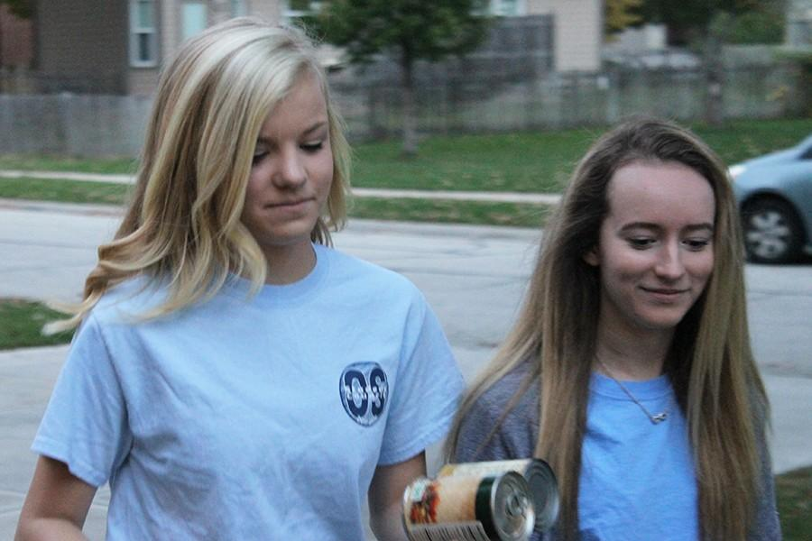 Korie Hutton and Katelyn Gravley, sophomores, go door to door to collect cans.