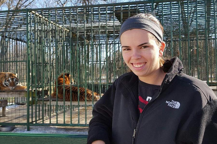 Beeler volunteers  at the Cedar Cove Feline Sanctuary, where they care for endangered big cats, some of which can be seen in the cages behind her. Beeler cleans these enclosures for the large cats as a part of her volunteer work.