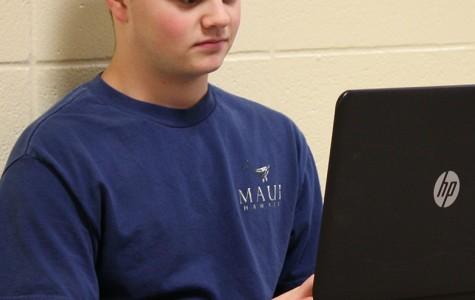 Ben Williams, senior, researching on his laptop for debate.