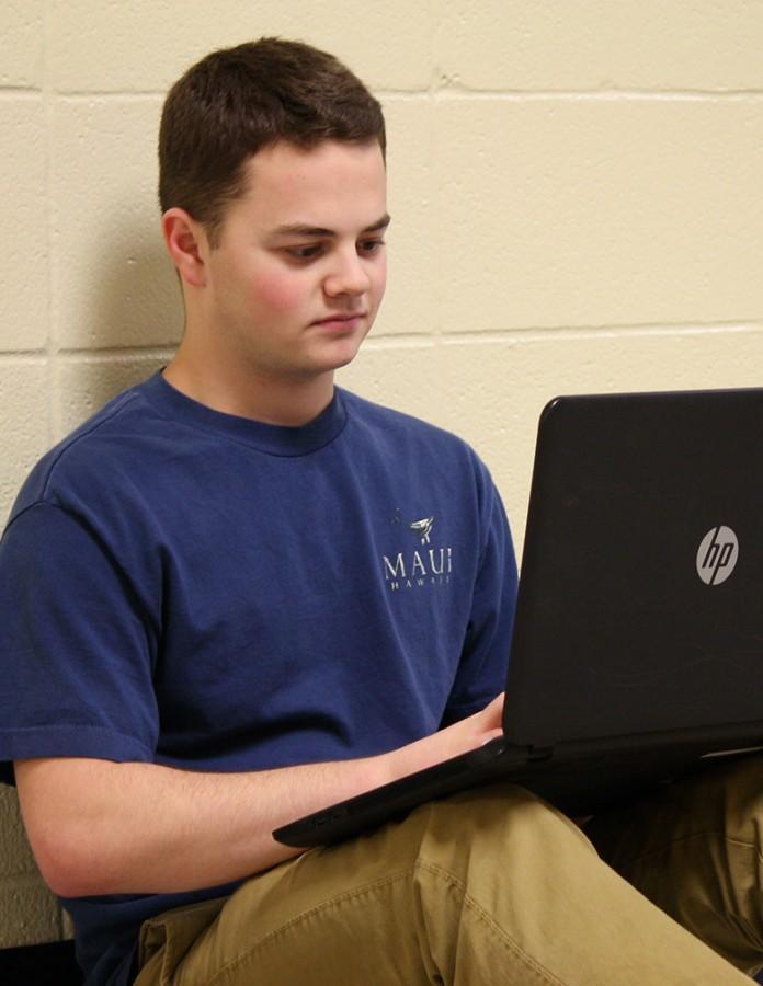 Ben+Williams%2C+senior%2C+researching+on+his+laptop+for+debate.