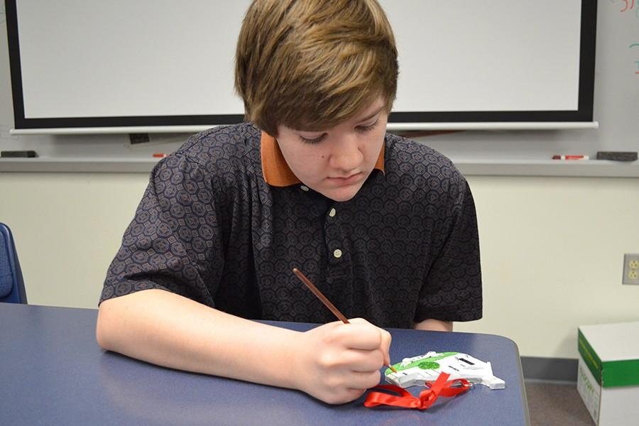 Taylor Thompson, senior, works diligently adding the final details on his handcrafted ornament. He models clay houses of his clients' homes. He has been making them for two years and mostly sells them around the holidays. He sells them through Etsy, and the finished ornaments are shipped to the clients.