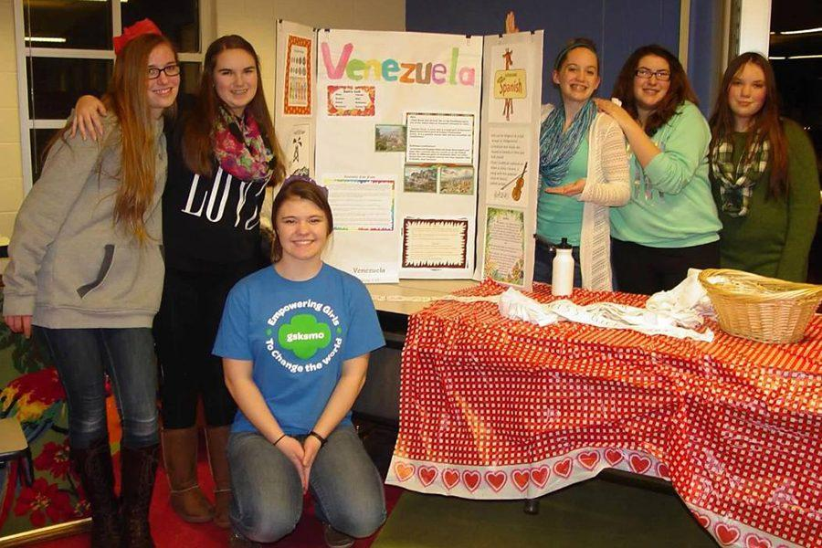 Jennifer Moore and Darriane Conely with their troop, presenting information about Venezuela