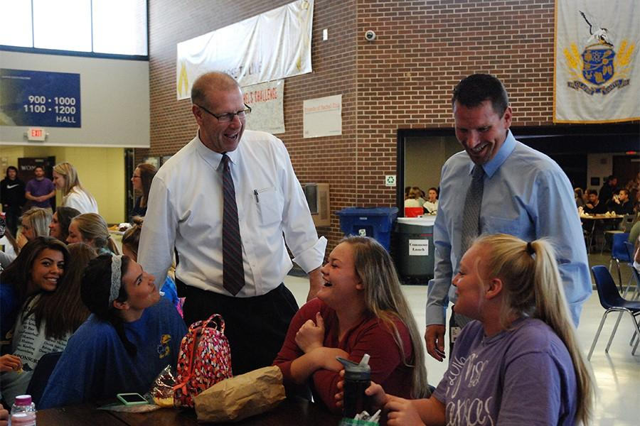 (From left to right) Lexie Storrer, Lindsey Delana and Kala Holder, seniors, laugh with Phil Clark, current principal, and Clint Albers, athletic director, during lunchtime. Clark will miss interacting with the students, but knows Albers will be a good choice to replace his position as principal.