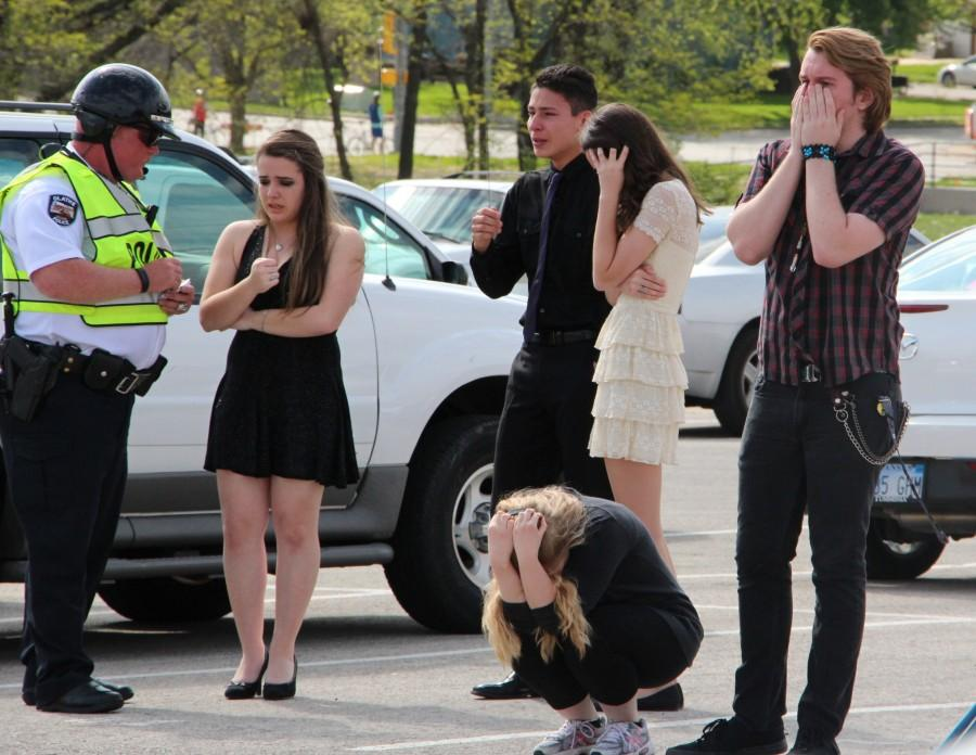 Prom group crying while being questioned by an officer about what happened.