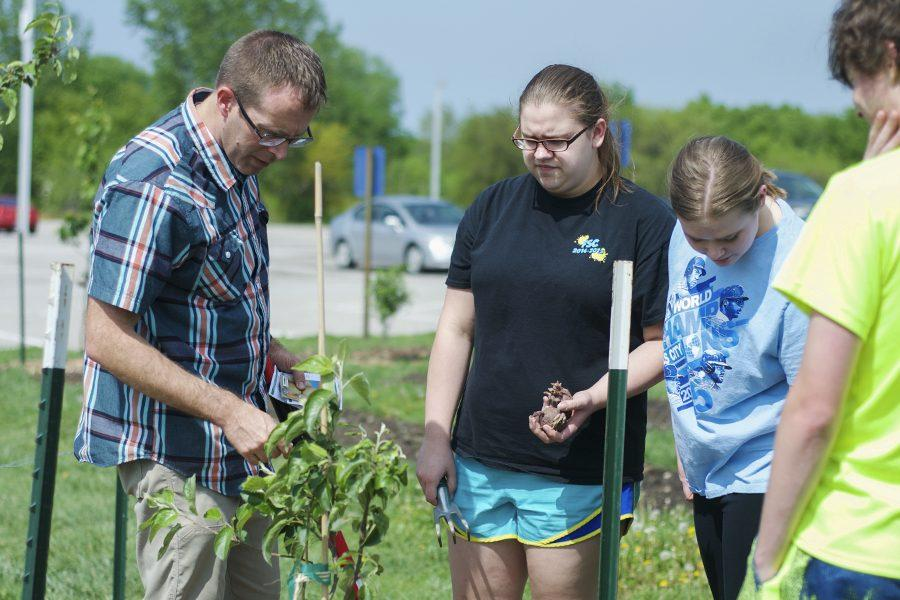 Mr. Witters and the Green Team check out the new fruit trees in the orchard.