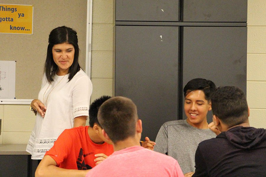 New English teacher, Victoria Palomino, watches students collaborate.