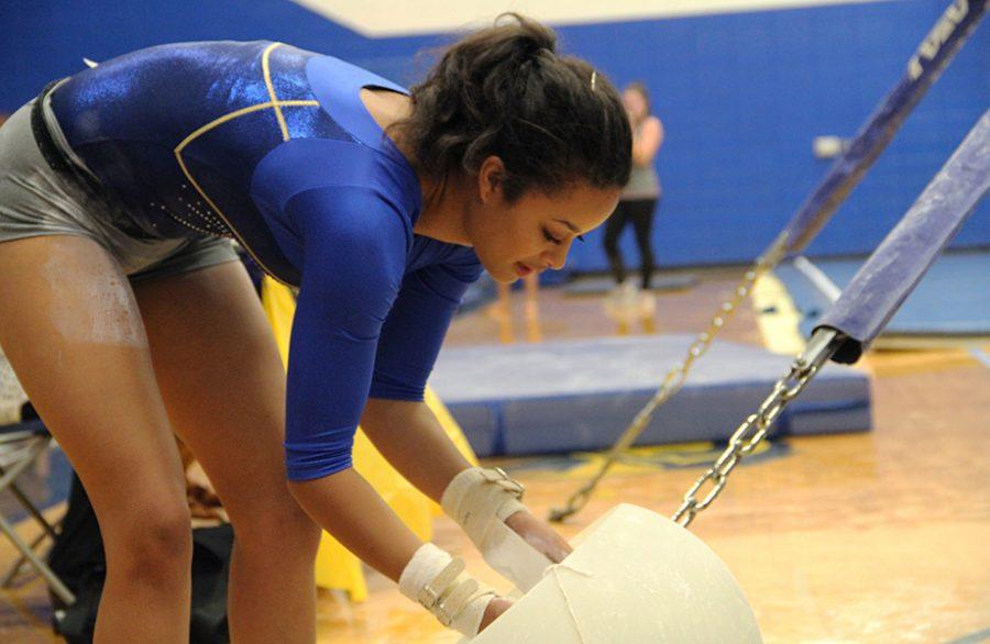 Serena Womack, sophomore, chalks up for her bar routine at a varsity gymnastics meet Sept. 20.