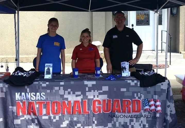 Breanna Salsmonson, senior, at a stand with two other National Guard members advertising for the National Guard itself.
