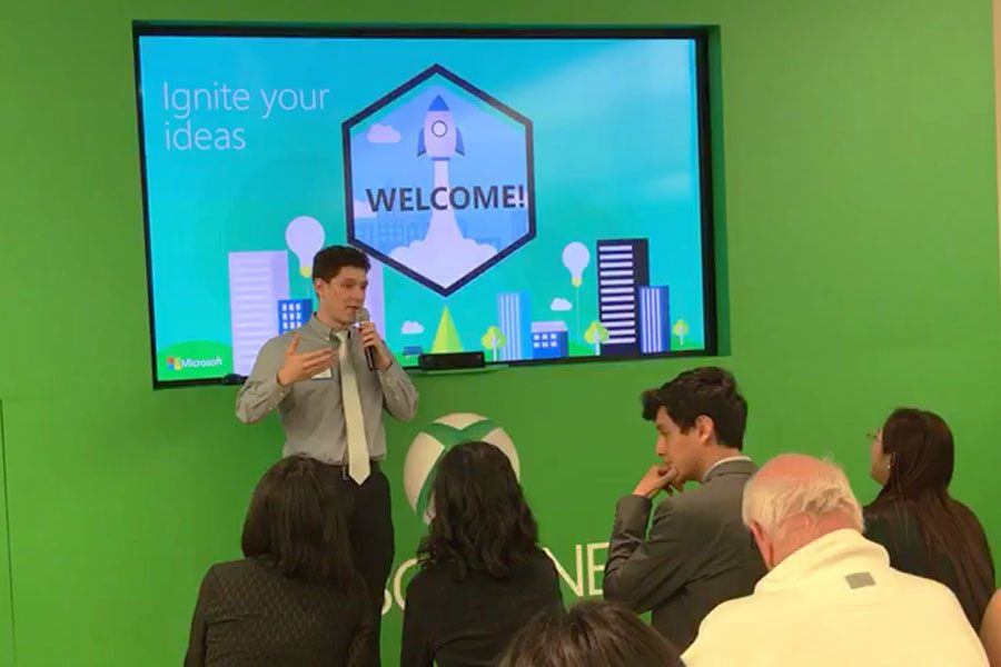 Daniel Moreira, senior, presenting his business idea in front of a crowd at Microsoft.