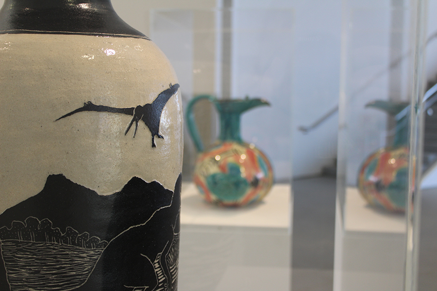 The vase is covered in scenes of prehistoric nature, all painted black. This includes painted trees, mountains and a Pterodactyl.