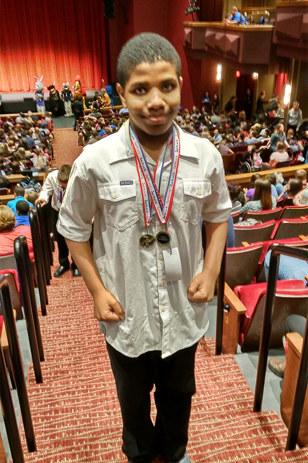 David Moses, freshman, with his medal for bagging groceries.