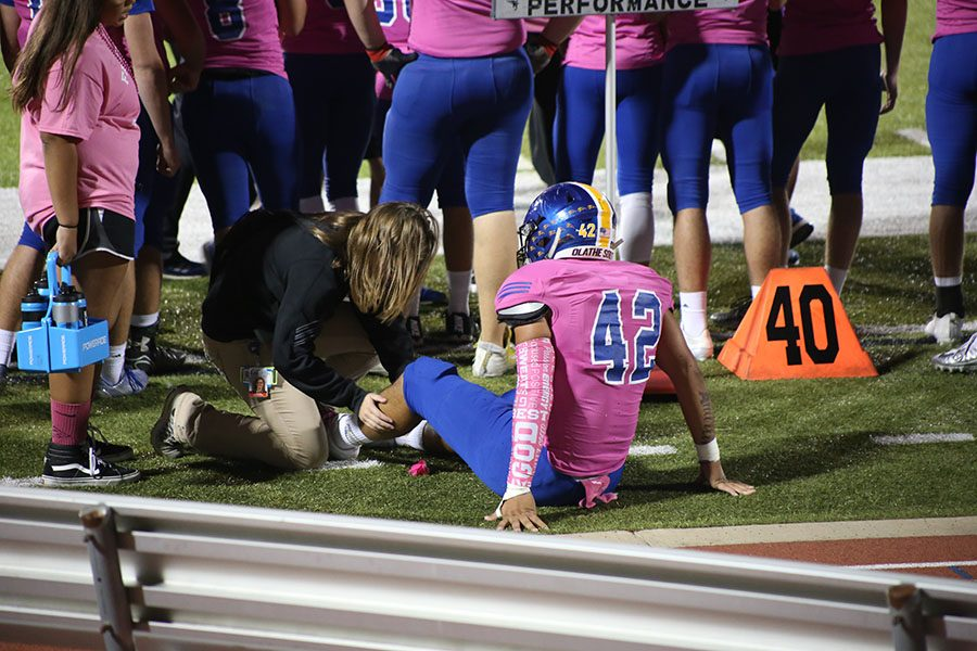 Adrian Garcia, senior, gets his leg checked by the athletic trainer at the football game against Shawnee Mission North on Oct. 20. Injured players go to physical therapy to stretch and strengthen muscles.
