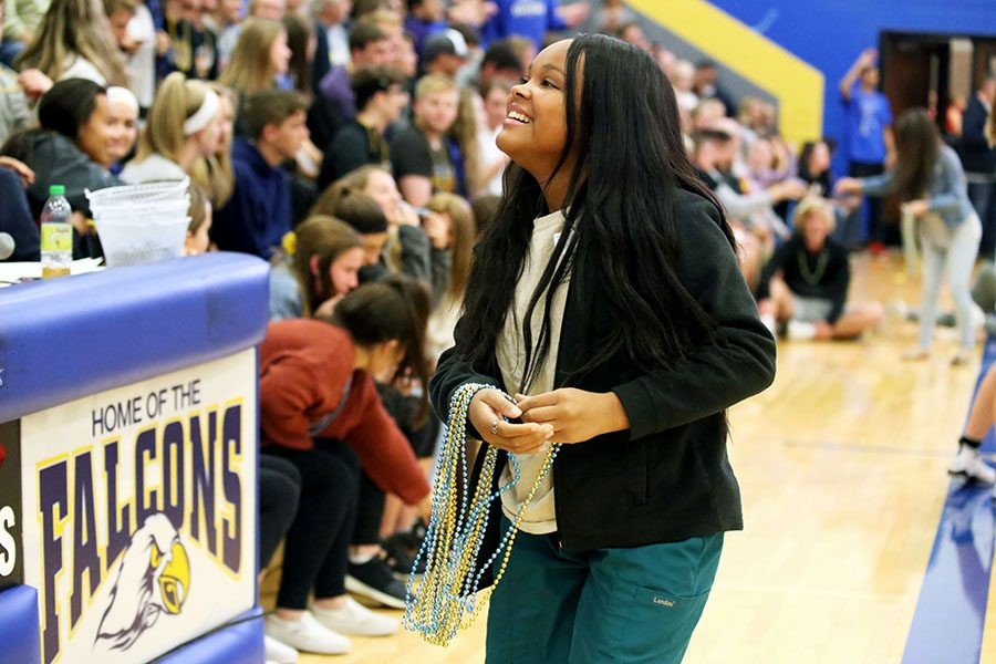 Chandler Patrick, senior, passes out blue and gold beads to the crowd to show support for the Lady Falcons.