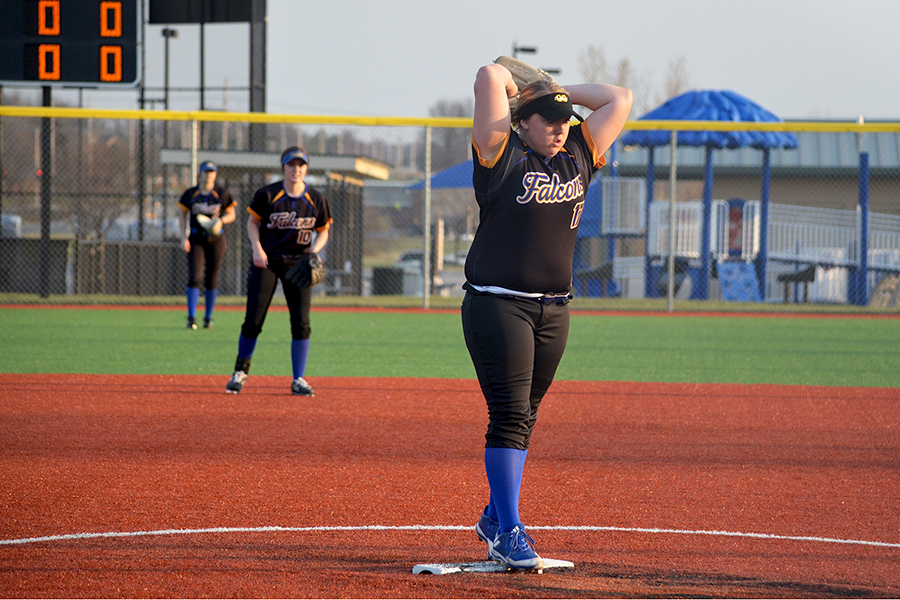 Maryssa Rollin, senior, in the windup prepared to devliver a pitch at CBAC for the softball team on April 5 against Olathe West. As the starting pitcher, lots of pressure rests on Rollin to do well.  Other players stood at the ready in the background, prepared to jump into action if the hitter sent the ball their way. Shortstop also must be ready if a player at first attempted to steal second base, working with the second baseman and catcher to prevent a base from being stolen.