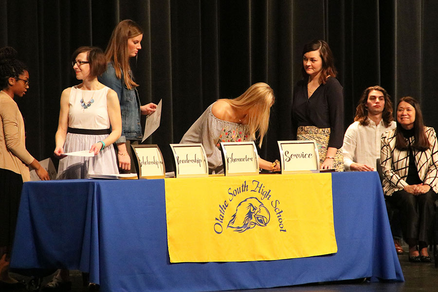 Students signing and accepting their certificate at the NHS induction ceremony.