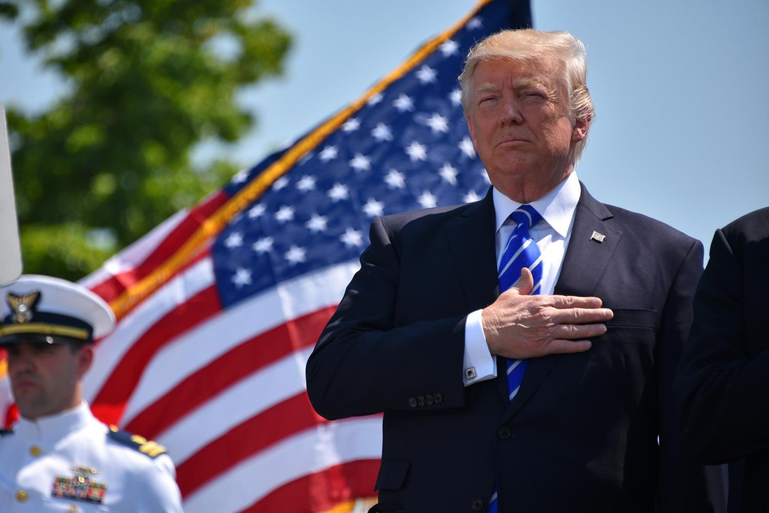 President Donald Trump, pictured holding his right hand over his heart to respect the American flag. Trump was investigated to see if he was eligible to be impeached and removed from the presidency.