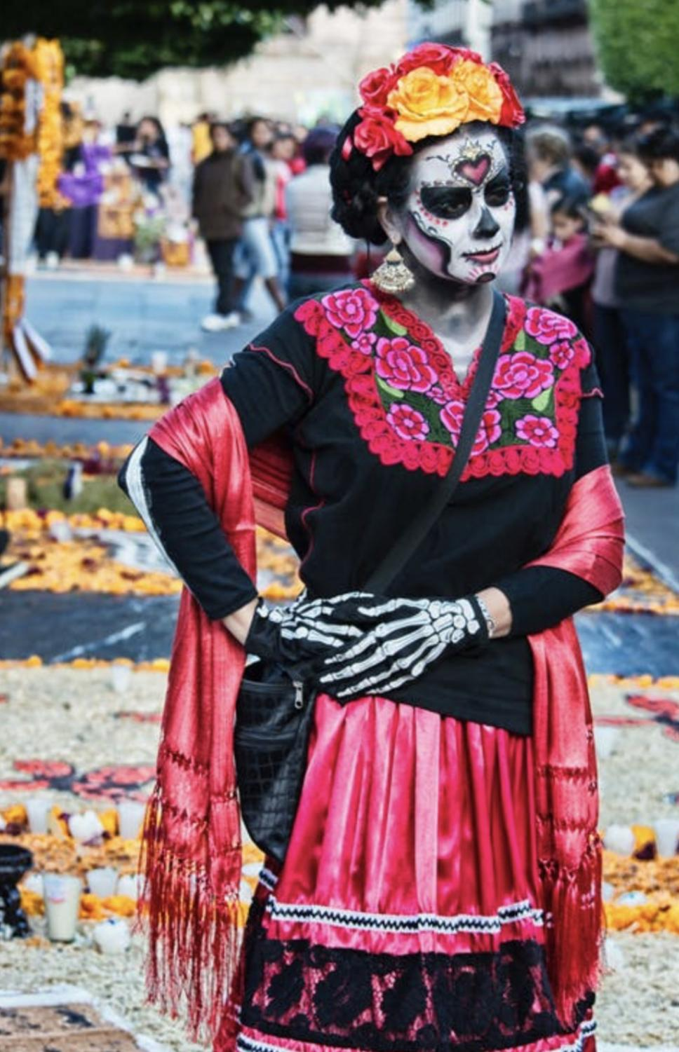 A woman dressed in traditional Day of the Dead attire participates in a celebration in Morelia, Mexico. The Day of the Dead is a traditional multi-day Mexican holiday which gathers families to honor their deceased family members and commemorate them with a decorated altar.