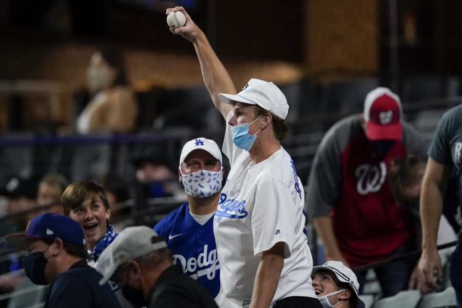 A fan shows off a foul ball that he caught at game one of the National League Championship Series. He was among the first fans to get a souvenir in 2020, as it was the first game of the year that MLB permitted fans to attend.