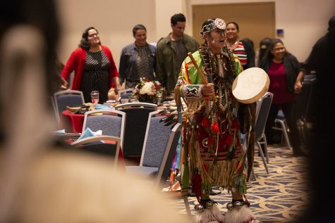 A performer at the 2019 Native American Heritage Month Celebration and Recognition event at California State University shows the crowd music, instruments and clothing from his culture.