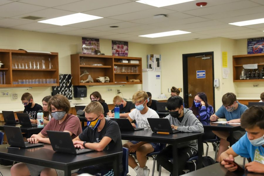 Students wear masks while working on laptops in Mr. Perkins biology class.