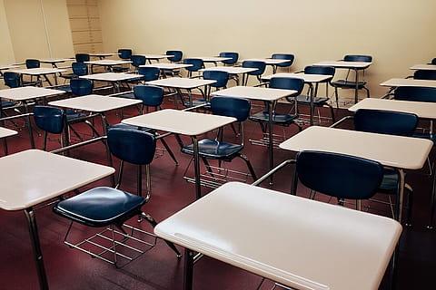 image of empty classroom full of desks taken by Piqsels